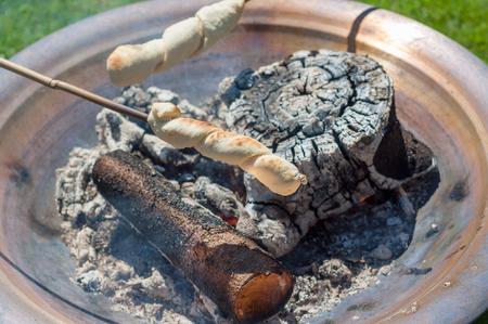 Bread baking over open fire - Snobrød Banco de Imagens - 95394113