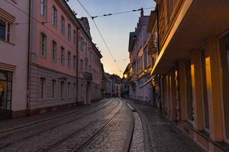 Street of the city center of freiburg, germany, in sunset with unique small stream (baechle)