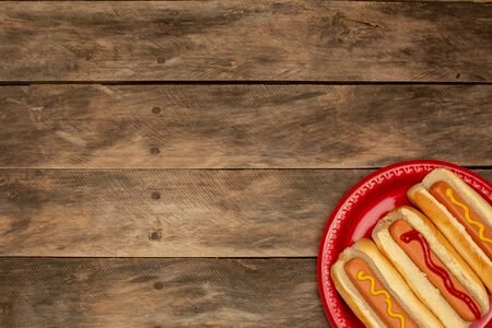 three hot dogs on a red plate and wooden table Standard-Bild