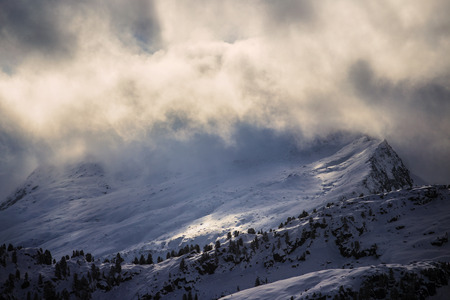 early morning clouds above mountain hill in winter scenery