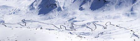 windy road crossing ski slopes of Sella Ronda resort in Dolomites