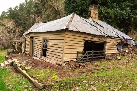 An old, abandoned farmhouse, crumbling into the earth. Photographed in the Southern Alps, New Zealand