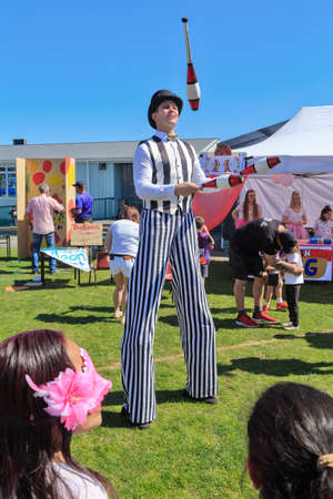 Tauranga, New Zealand - September 21 2019: A stilt walker in black and white striped clothing, juggling clubs at a village fair