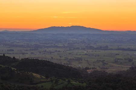 A view across the farmland of the Waikato Region, New Zealand, at sunset, from the Kaimai Mountains. On the horizon is Maungatautari, or Sanctuary Mountain
