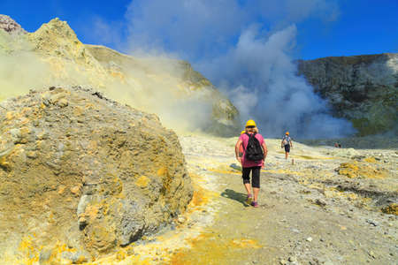 Tourists walking through the yellow, sulfurous landscape of White Island, an active volcano off the coast of New Zealand, towards the steaming crater lake