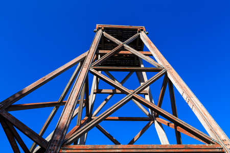 An old mining headframe. This wooden structure stood at the top of a mine shaft and was used to transport miners and ore into and out of the mine Zdjęcie Seryjne