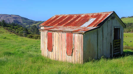 A rustic old wooden and corrugated iron barn on a farm in New Zealand hill country