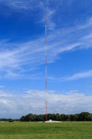 An AM radio transmitter tower, a long, thin structure standing straight up in a field