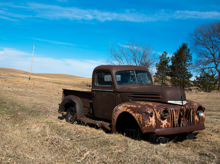 Rusty old truck with bullet holes in the windshield abandoned in field. Archivio Fotografico