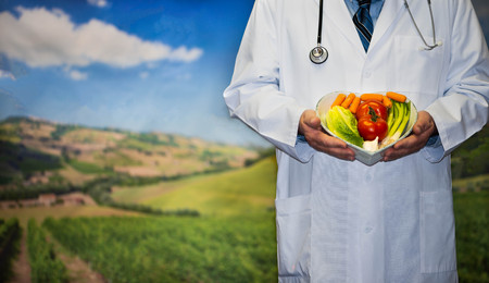 Doctor standing in country setting holding a heart shaped dish full of veggies Stock fotó