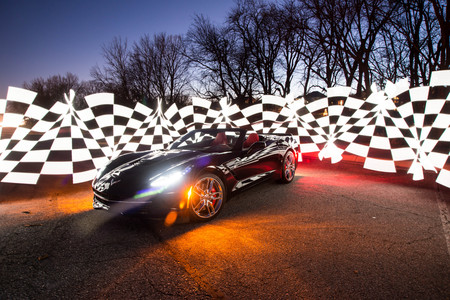Black C7 corvette on display at night with checkered pattern around it.