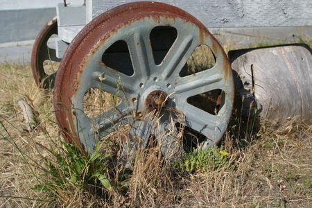 rusting: an old wagon wheel, sits rusting