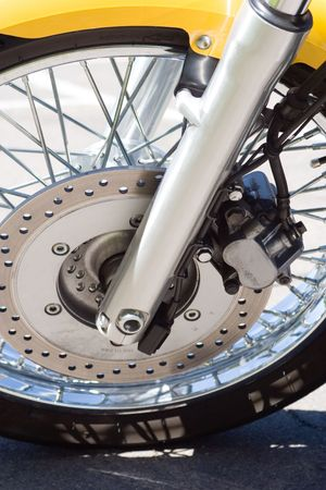 the front tire and disc brake of a yellow motorcycle Stock Photo