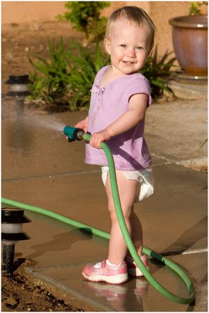 little girl waters using a hose Stock Photo - 382606
