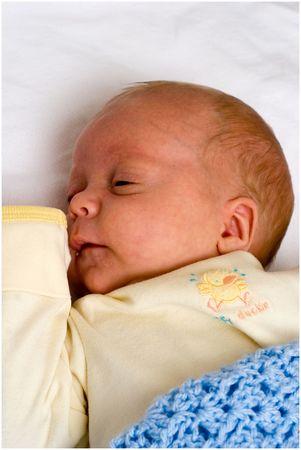 Bambino in giallo poggiato sul lenzuolo bianco  Archivio Fotografico - 382603