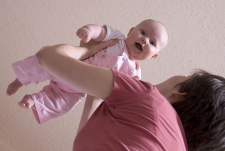 adore: mother swings baby into the air Stock Photo