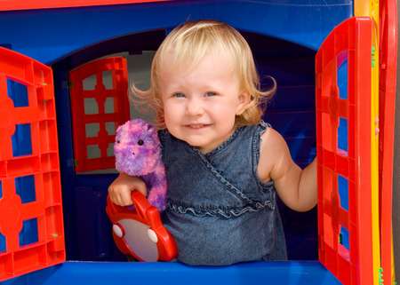 little girl peaks out the window of toy house Reklamní fotografie