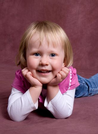 little girl lays on dark backdrop for a simlpe portrait Stock Photo - 2060728