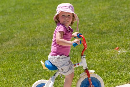 young girl rides a tricycle around the local park Stock Photo