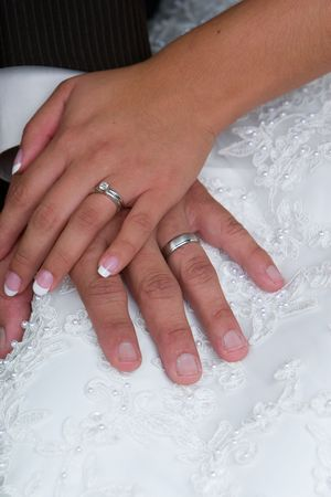 Bride and groom sit and show off the newly exchanged rings Stock Photo