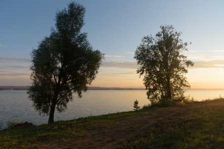 Trees beside lake in Votkinsk at sunset Stock Photo