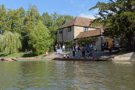 CAMBRIDGE, UK - SEPTEMBER 16, 2018: Tourists at Trinity College Punt House hiring punt boats 報道画像