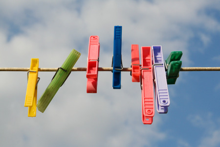 Coloured pegs on a washing line with sky behind