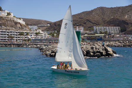 PUERTO RICO, GRAN CANARIA - MARCH 17, 2015 - Group of children on a yacht enjoying learning how to sail