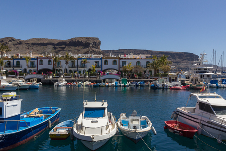 PUERTO DE MOGAN, GRAN CANARIA - MARCH 17, 2015 - Boats in the habour with colorful buildings behind Editorial