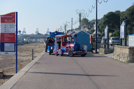 FELIXSTOWE, UNITED KINGDOM - OCTOBER 20, 2018 - Seafront train driving along the prom with people on-board