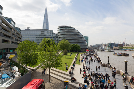 LONDON, UNITED KINGDOM  - MAY 15, 2015 - The Southbank with many people walking with City Hall and The Shard in the background Editorial