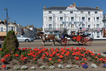 GREAT YARMOUTH, UNITED KINGDOM - JULY 14, 2018 - Horse and cart with tourists passing the Royal Hotel on Great Yarmouth sea front Editorial