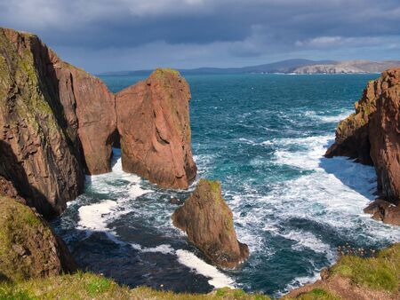 Sea cliffs and a natural arch near North Ham on Muckle Roe, Shetland, Scotland, UK