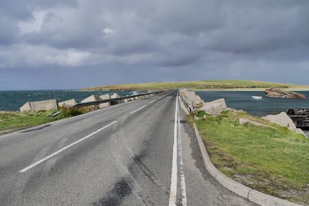 A roadway across a Churchill Barrier in the Orkney Islands in Scotland, UK