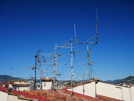 Television aerials against a blue sky on terracotta roofs in Florence, Italy