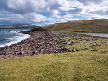 Rocky debris on the beach that separates Loch Croo from the sea at Eshaness, Shetland, Scotland, UK