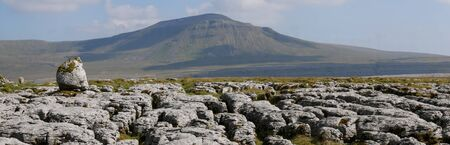 Limestone pavement - an area of limestone eroded by water - on Scales Moor in the Yorkshire Dales, UK, with Ingleborough in the background Banco de Imagens