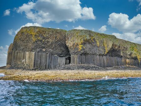 Columnar jointed volcanic basalt rocks in which the vertical joints form polygonal columns, on the island of Staffa in the Inner Hebrides, Scotland, UK