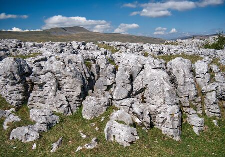 Limestone pavement - an area of limestone eroded by water - on Southerscale Scars in the Yorkshire Dales, UK, with Whernside in the background