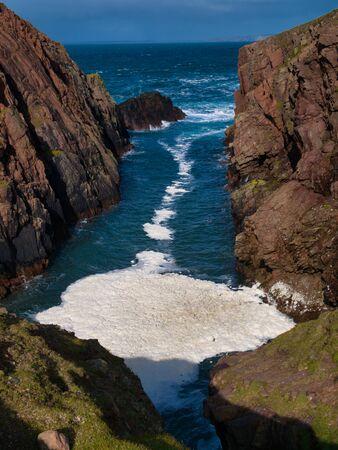 Sea spume or sea foam formed in West Ness Geo near North Ham on the island of Muckle Roe in Shetland, Scotland, UK. Sea foam, ocean foam, beach foam, or spume is a type of foam created by the agitatio