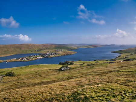 A view of Weisdale Voe on the west of Mainland, Shetland, Scotland, UK, taken on a sunny day with a blue sky and light clouds the houses at Kalliness and the Loch of Hellister appear on the left.