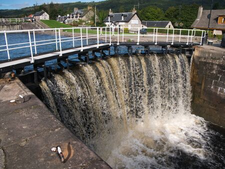 Water cascades over the lock gates at Fort Augustus on a sunny day in summer. The lock in the background is full, ready to empty to raise the level in the lock in the foreground and to carry boats to the higher level.