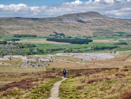 A lone walker on a stone path above the limestone pavement of Southerscales Scars, heading to Whernside in the Yorkshire Dales in the UK Banco de Imagens