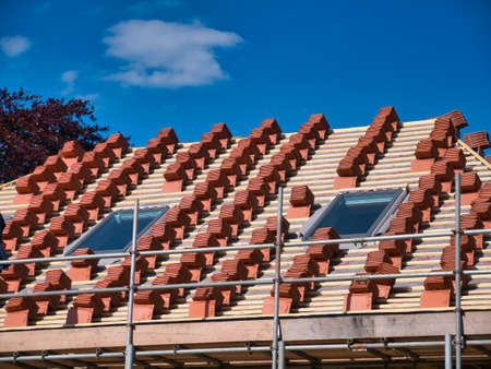 A house roof under construction, showing stacks of terracotta tiles ready for fitting on wooden battens. Taken on a sunny day with a blue sky.