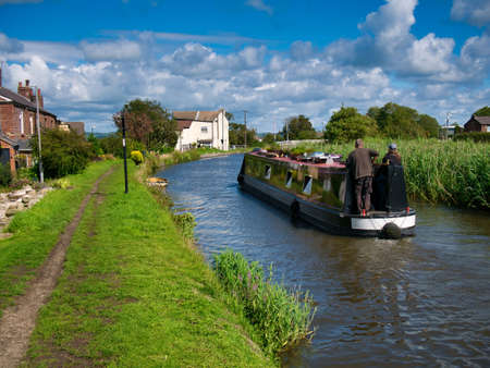 Holidaymakers on a narrowboat cruising on the Leeds to Liverpool Canal in tranquil, rural Lancashire. Taken on a sunny day in summer.