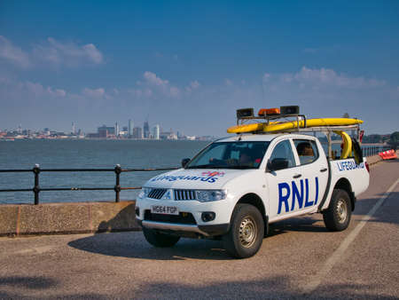 An RNLI Team on standby to help swimmers in distress at New Brighton on the River Mersey - the UNESCO listed historic Liverpool waterfront appears in the background.