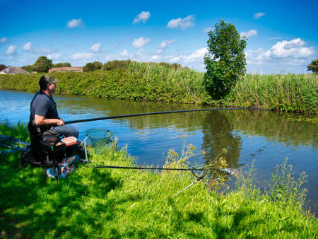 A single angler fishes for carp on the Leeds Liverpool Canal with a long carbon fibre pole that reaches across the water. A landing net and keep net are visible.