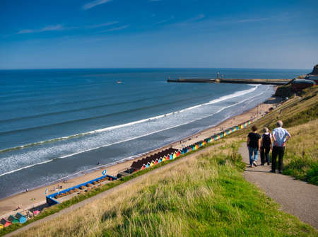 Tourists on a path overlooking colourful beach huts, the coast and harbour piers at Whitby, North Yorkshire, UK - taken on a sunny day at the end of summer