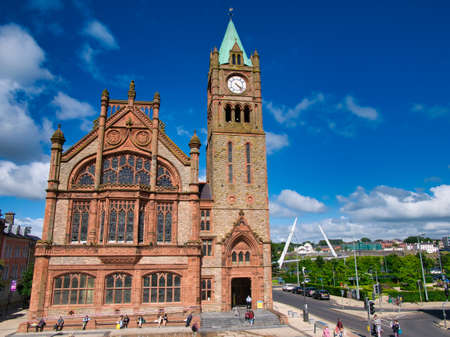 The Guildhall in Derry ~ Londonderry with the Peace Bridge in the right background. Taken on a sunny day with blue sky and white clouds.
