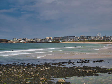Across West Strand Beach on a sunny day in summer, a view of the popular tourist destination of Portrush in Antrim, Northern Ireland, UK. Standard-Bild